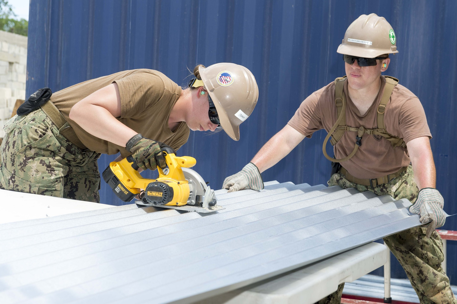 Women in trades cutting sheet metal